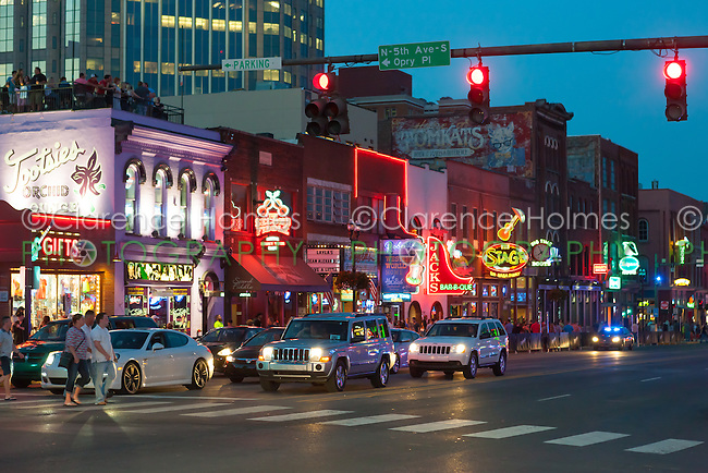 Neon signs light the Honky-tonks, including Tootsies Orchid Lounge and Robert's Western World, and other tourist attractions at twilight on Lower Broadway in Nashville, Tennessee.