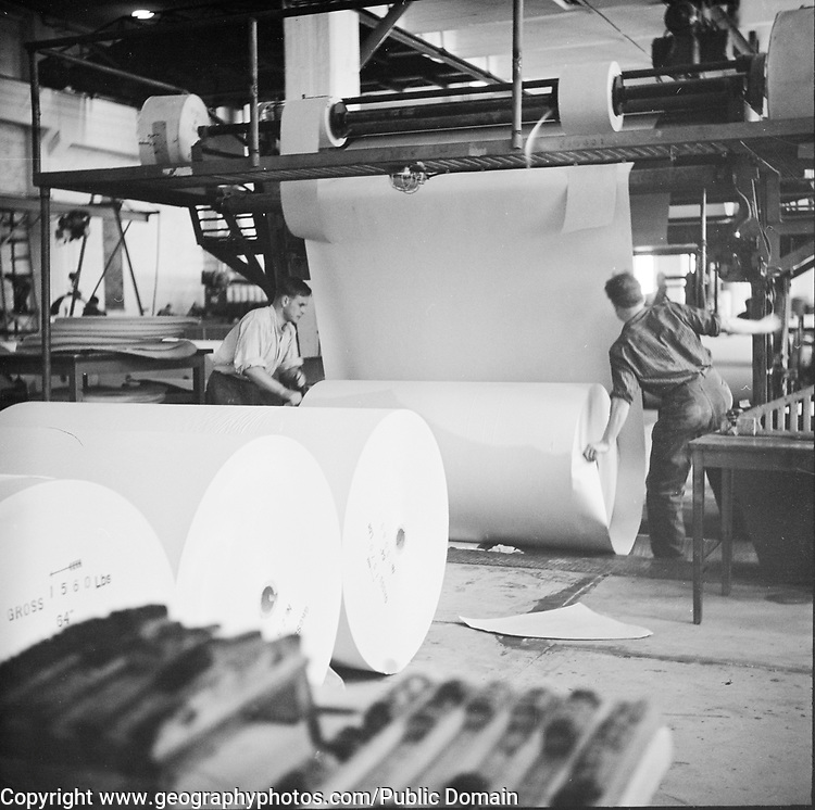 Two male employees moving the finished paper roll, Summa paper mill, Vehkalahti, Kymenlaakso, Finland, 1957