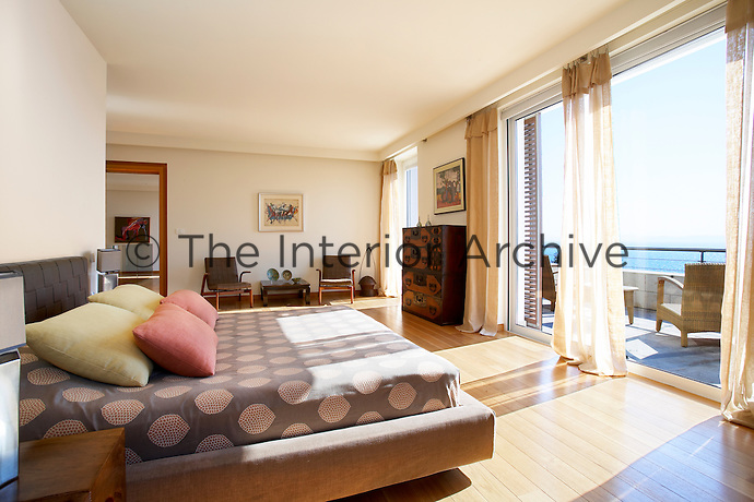A spacious bedroom with a wood floor and sliding glass doors that open onto a private balcony.