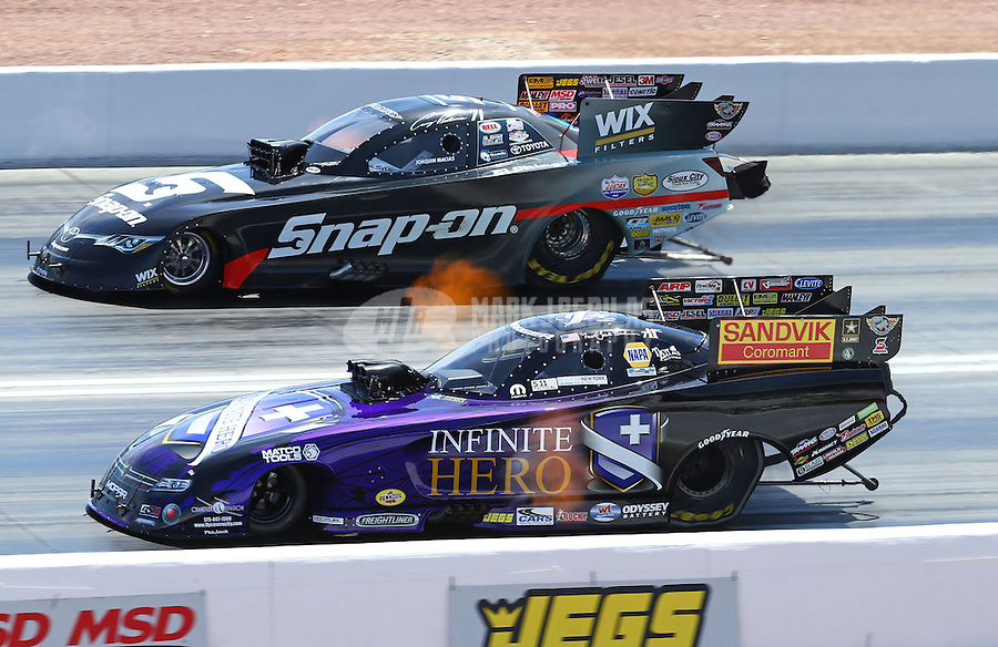 Apr 12, 2015; Las Vegas, NV, USA; NHRA funny car driver Jack Beckman (near lane) races alongside Cruz Pedregon during the Summitracing.com Nationals at The Strip at Las Vegas Motor Speedway. Mandatory Credit: Mark J. Rebilas-