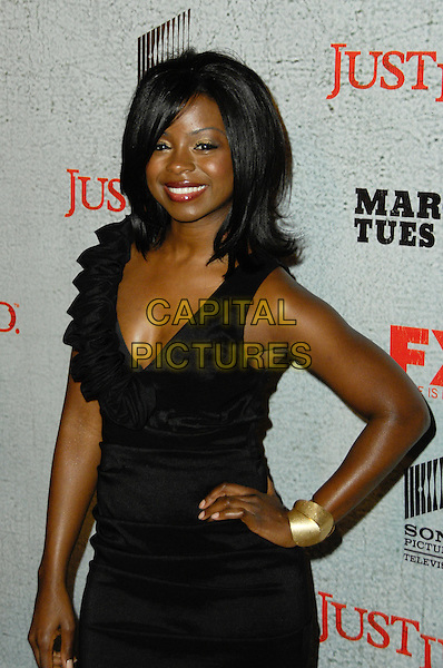 ERICA TAZEL.Arrivals to the premiere screening of the FX original drama series, Justified, at the Directors Guild of America. Los Angeles, CA, USA, March 8th, 2010..half length black sleeveless dress hand on hip ruffle gold bracelet .CAP/CEL/RL .©Rich Linton/CelPh/Capital Pictures