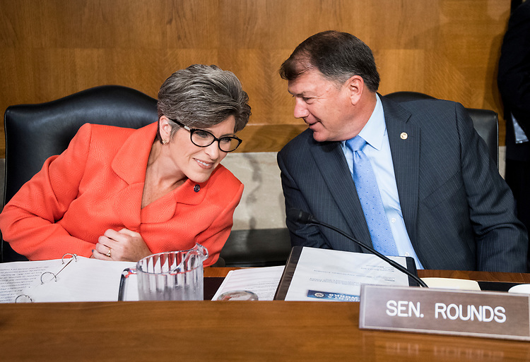 "UNITED STATES - AUGUST 1: From left, Sen. Joni Ernst, R-Iowa, and Sen. Mike Rounds, R-S. Dak., talk before the start testimony from Andrew Wheeler, acting administrator at the Environmental Protection Agency, prepares to testify during the Senate Committee on Environment and Public Works hearing on ""Examining EPA's Agenda: Protecting the Environment and Allowing America's Economy to Grow"" on Wednesday, Aug. 1, 2018.  (Photo By Bill Clark/CQ Roll Call)"