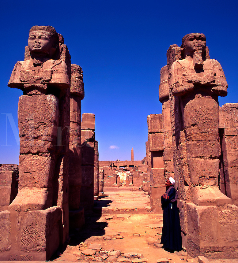 Egyptian Guide looking at Statues of Ramses One and Two. Karnak Temple. Luxor. Egypt.