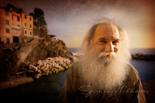 A Native Coastal man on the town wall over the sea in Cinque Terre Italy.