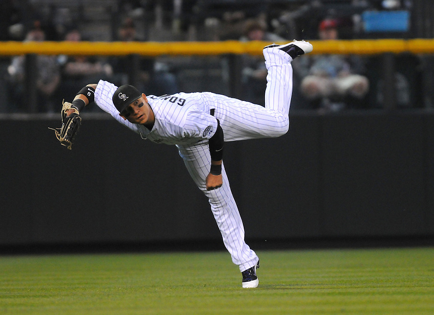 18 APRIL 2011: Colorado Rockies left fielder Carlos Gonzalez (5) attempts an outfield assist during a regular season game between the San Francisco Giants and the Colorado Rockies at Coors Field in Denver, Colorado. The Giants beat the Rockies 8-1. *****For Editorial Use Only*****