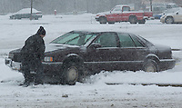 A friend attempts to help a driver clear his car from atop a parking lot berm in Columbus, Ohio,  that had been obscured by a snowstorm that moved across central Ohio Wednesday, December 22, 2004.