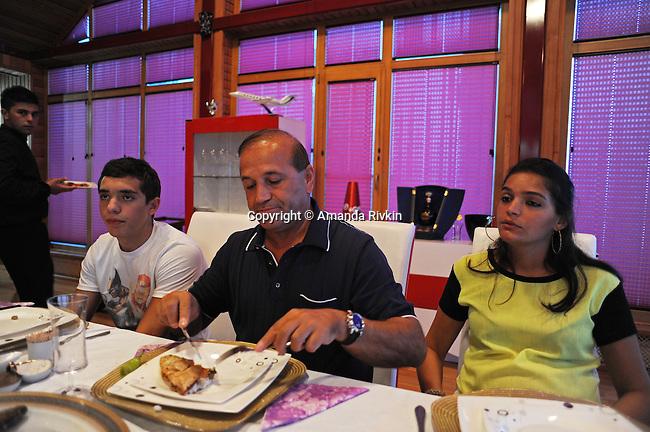 Ibrahim Ibrahimov (center) sits at the dinner table and eats fish with his son Huseyn Ibrahimov, 18, and daughter Ilkana Ibrahimova, 22, in his home between Sangachal and Sahil, Azerbaijan on August 16, 2012.