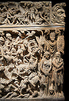 Roman Sarcophagus with detailed relief sculptured panels with battle scenes. This large sarcophagus which was found in 1931 near the Tiburtina, in the eastern suburbs of the ancient city, shows on its front a symbolic battle, staged on two levels. This composition focuses on the progress of the Roman horseman, depicted in the guise of a universal victor, in a melee of soldiers, spears and horses; the Romans are delivering savage blows, devastating their enemies. The bloody scenes are framed by two pairs of enslaved barbarians, whose afflicted demeanour expresses the suffering which comes to those who rebel against the dominion of Rome. The dramatic animation of the combat emphasised by the deep chiaroscuro obtained by a skilful feat of carving. The low relief on the sides of the sarcophagus shows events subsequent to the encounter; on one side barbarian prisoners cross the river on the other chiefs submit to the Roman officials. The freeze on the lid, between two corner masks, celebrates the dead man and his wife, presented in the centre is the act of 'dextarum iunctio'; on the left, the women exercises her 'virtue' in the house, educating her children; on the right, the, after his warlike activities, receives his 'clementia'. The faces of the principle characters remain incomplete, awaiting the carving of the features of the dead people. The decoration of the sarcophagus, inspired by many scenes on the Antonine Column, can be dated to around 180AD. The military insignia represented on the upper edge of the casket - the eagle of the Legio III Flavia and the boar of the Legio I Itlaica - enable us perhaps to identify the dead man as Aurelius Iulius Pompilius, an official of Marcus Aurelius in command of two cavalry squadron on detachment to those two legions during the war against Marcomanni (1720-175AD). National Roman Museum, Rome, Italy