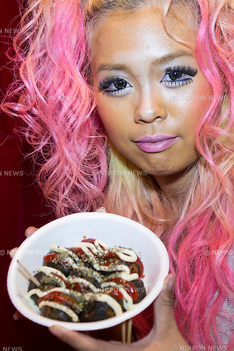 Pomitan (24), store manager, shows to the camera the bar's original food Ganguro Balls at the Ganguro Cafe &amp; Bar in the Shibuya shopping area on September 4, 2015. <br /> <br /> Ganguro is an alternative Japanese fashion trend which started in the mid-1990s where young women, rebelling against the traditional idea of Japanese beauty, wore colorful make-up and clothes and had dark-skin.<br /> <br /> 10 Ganguro fashion girls work in the new bar, which offers original Ganguro Balls (fried takoyaki style sausage balls in black squid ink batter) on its menu. Ganguro Caf&eacute; &amp; Bar also offers special services such as Ganguro make-up and the chance to take purikura (photo booth pictures) with staff and to look like a Ganguro girl walking around the Shibuya streets.<br /> <br /> The bar is popular with both Japanese and foreigners and has menus translated in English. (Photo by Rodrigo Reyes Marin/AFLO)