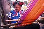 An indigenous Tzotzil woman who was expelled from her community of San Juan Chamula for being evangelical, as opposed to Catholic, weaves on her backstrap loom near San Cristobal Cathedral in Chiapas, Mexico.