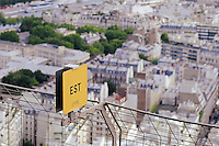 East side signpost on Eiffel tower 2nd level with Paris historical buildings in background