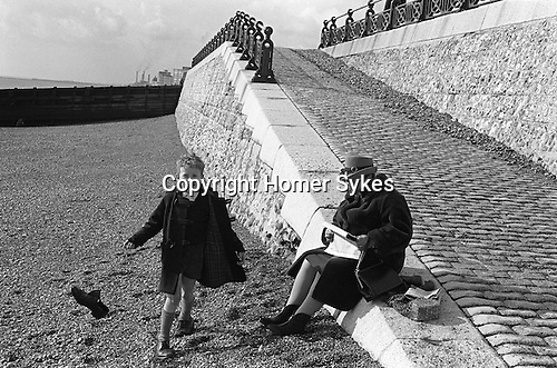 Young boy swinging his shoe by it laces. Brighton Beach Sussex England 1970