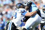 30 November 2013: Duke's Kelby Brown (59) tackles UNC's Marquise Williams (right). The University of North Carolina Tar Heels played the Duke University Blue Devils at Keenan Memorial Stadium in Chapel Hill, NC in a 2013 NCAA Division I Football game. Duke won the game 27-25.