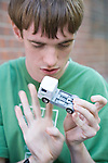 Teenage boy with Autism playing with toy truck. MR
