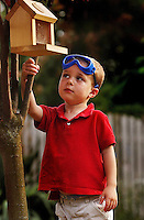 A young boy inspects the bird feeder he helped build.