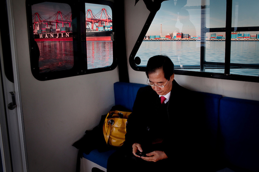 CREDIT: Daryl Peveto / LUCEO for The Wall Street Journal.Assignment: 10113  Slug: KORDEAL..Long Beach, California, January 24, 2011 - Han Duk-soo, South Korea's Ambassador to the United States reads email during a tour of the Port of Long Beach along with Chamber of Commerce representatives, South Korean advisors and local businessmen. The delegation was in town as part of a sustained effort since 2007 to sell the idea of the U.S.-Korea Free Trade Agreement to the US. Final language is still being worked out, but the agreement could come to a vote in the next few weeks. ..The U.S.-Korea Free Trade Agreement would eliminate tariffs on 95% of U.S. goods within five years of its signing and could boost U.S. exports by $11 billion annually, the International Trade Commission estimates. It would also reduce trade restrictions and tariffs on U.S. auto and beef exports while continuing American tariffs on South Korean autos for a limited time. Southern California would almost certainly be a major beneficiary. Nearly $16 billion in goods moved between South Korean and Southland ports in 2009. The Los Angeles area is home to an estimated 600,000 Korean Americans, many of whom have strong business ties to their homeland and are heavily invested in the local economy. Southern California's entertainment industry also supports the pact, which would clamp down on unauthorized copying and sharing of music and videos in South Korea, where piracy is a serious problem..