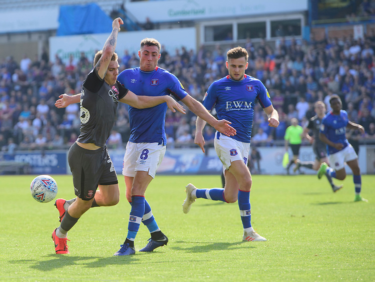 Lincoln City's Harry Anderson vies for possession with Carlisle United's Mike Jones<br /> <br /> Photographer Chris Vaughan/CameraSport<br /> <br /> The EFL Sky Bet League Two - Carlisle United v Lincoln City - Friday 19th April 2019 - Brunton Park - Carlisle<br /> <br /> World Copyright © 2019 CameraSport. All rights reserved. 43 Linden Ave. Countesthorpe. Leicester. England. LE8 5PG - Tel: +44 (0) 116 277 4147 - admin@camerasport.com - www.camerasport.com