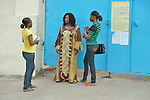 Isabella Washington (right), 26, and Catherine Hill (left), 28, talk with Alfreda Anderson, the coordinator of ministries for United Methodist Women in Liberia. They are talking in front of United Methodist University in Monrovia, where Washington and Hill are studying with help from scholarships from United Methodist Women.