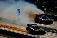 Sept. 18, 2010; Concord, NC, USA; NHRA funny car driver Tony Pedregon (near) and Matt Hagan do their burnouts during qualifying for the O'Reilly Auto Parts NHRA Nationals at zMax Dragway. Mandatory Credit: Mark J. Rebilas /