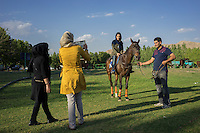 June 12, 2014 - Tehran (Iran). A young girl is photographed riding a horse during the 83rd Federation of the International Polo Ambassadors' Cup, organised in a field located in the south of Tehran. © Thomas Cristofoletti / Ruom