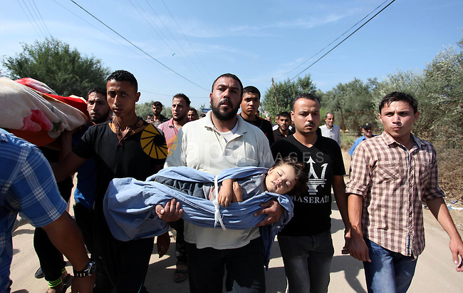 """Relatives carry the body of two-year-old Palestinian girl Rahaf, during the funeral of the toddler and her pregnant mother on October 11, 2015, at the al-Nusairat refugee camp, in central Gaza Strip. A pregnant Palestinian mother and her toddler daughter were killed in the air strike in the Zeitun sector south of Gaza City while three others were still trapped under the ruins of a house, medical sources said. Israel said it had targeted """"two Hamas weapon manufacturing facilities"""" in response to two rocket launches at Israel the day before. Photo by Ashraf Amra"""