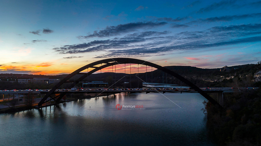 A colorful sunset paints the sky across the 360 Pennybacker Bridge, built in 1982, the bridge spans across Lake Austin, Colorado River.