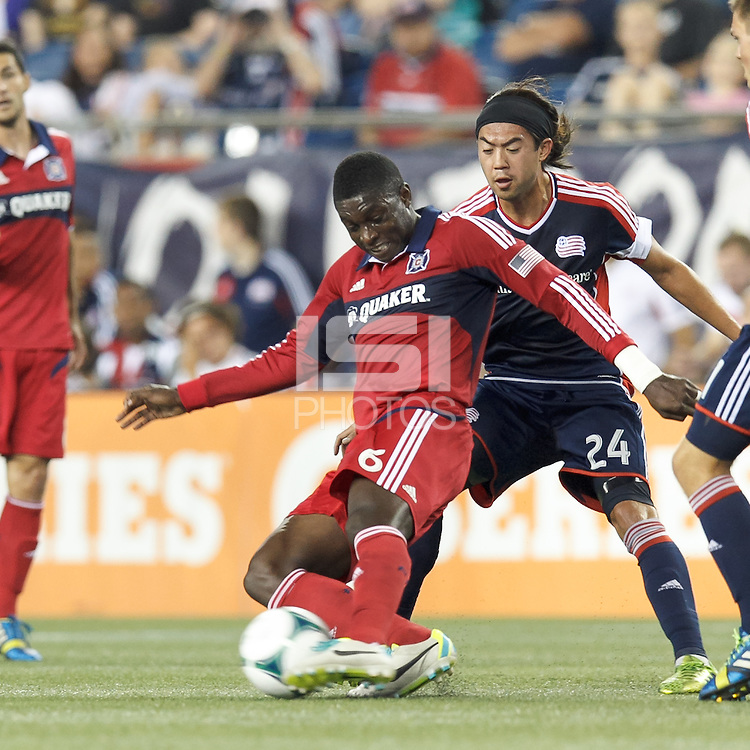 Chicago Fire defender Jalil Anibaba (6) works to clear ball as New England Revolution midfielder Lee Nguyen (24) pressures. In a Major League Soccer (MLS) match, the New England Revolution (blue) defeated Chicago Fire (red), 2-0, at Gillette Stadium on August 17, 2013.