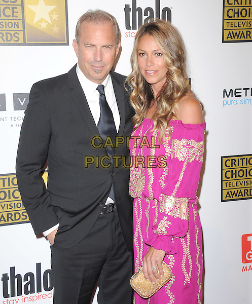 Kevin Costner & Christine Baumgartner.The 2nd Annual Critics' Choice Television Awards  held at The Beverly Hilton in Beverly Hills, California, USA..June 18th, 2012.half length black suit tie white shirt pink dress gold embroidered off the shoulder clutch bag married husband wife soul patch facial hair   .CAP/RKE/DVS.©DVS/RockinExposures/Capital Pictures.