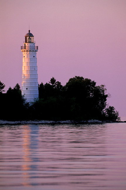 The Cana Island Lighthouse tower rises from the trees on the Lake Michigan shore at Sunset