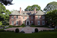 The front of the house is approached by a driveway lined in red brick and framed with hedges of clipped box