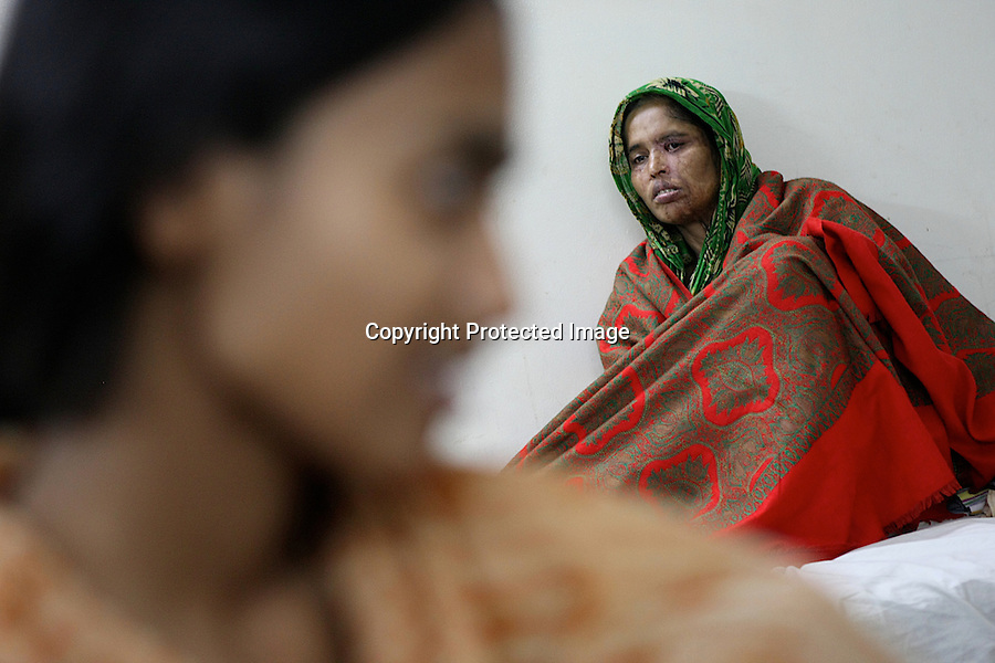"Women are chatting in a bedroom at Acid Survivors Foundation center in Dhaka. Dr Imtiaz, who has been working at Acid Survivors Foundation since the beginning, explains : ""Sometimes, the whole family is being attacked. In a single incident we are now getting five or six patients. Previously it was one incident, 1 patient. Men are now under attacks as well. We have70% women, 30% men""..Bangladesh - 2009"