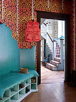 The 1960s style wallpaper in the cloakroom, adjoining the main entrance hall, contrasts with a  settle upholstered in turquoise fabric