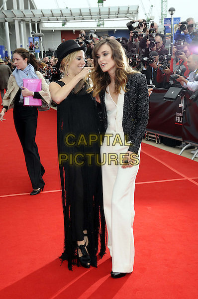 "SIENNA MILLER & KEIRA KNIGHTLEY.Arrive at the premiere for ""The Edge Of Love"" at the 62nd Edinburgh International Film Festival,  Edinburgh, Scotland..June 18th, 2008.full length black white dress hat tassels jacket trousers pant suit catsuit jumpsuit brown clutch bag hand hand bending funny .CAP/FIN.©Steve Finn/Capital Pictures."