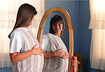 young pregnant woman holding her swollen belly admiring herreflection in bedroom mirror