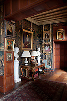 Tudor and Jacobean portraits of King Edward VI, Anne of Denmark and Katherine Carey, Countess of Nottingham, hang in a tapestried hallway