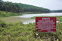 A warning sign written in Malay. The first part is loosely translated as Beware - do not trespass in water area. Enter at your own risk. A lake full of rainwater is used for irrigation on the plantation and in the oil mill. Palm trees line its banks. The Sindora Palm Oil Plantation, owned by Kulim, is green certified by the Roundtable on Sustainable Palm Oil (RSPO) for its environmental, economic, and socially sustainable practices. Johor Bahru, Malaysia