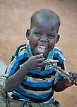 Three-year old Kaban Kon relishes the asida he eats from the stick his mother used to stir the pot in a camp for over 5,000 internally displaced persons in an Episcopal Church compound in Wau, South Sudan. Most of the families here were displaced by violence early in 2017, after a larger number took refuge in other church sites when widespread armed conflict engulfed Wau in June 2016.<br /> <br /> Made from sorghum or other grains, asida is a kind of thick porridge or mush, called ugali or other names in other parts of Africa.<br /> <br /> Norwegian Church Aid, a member of the ACT Alliance, has provided relief supplies to the displaced in Wau, and has supported the South Sudan Council of Churches as it has struggled to mediate the conflict in Wau. <br /> <br /> Parental consent obtained.