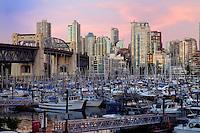 Vancouver area of Burrard bridge showing apartment, office blocks marina and Burrard bridge at dusk. British Columbia, Canada