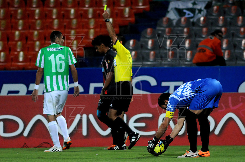 MEDELLIN - COLOMBIA -05-04-2014: Luis Sanchez, arbitro muestra tarjeta amarilla a Luis Paez jugador de  de Atletico Nacional durante partido Atletico Nacional y Atletico Junior por la fecha 15 de la Liga Postobon I 2014 en el estadio Atanasio Girardot de la ciudad de Medellin. / Luis Sanchez, referee, shows yellow card to Luis Paez player of Atletico Nacional during a match Atletico Nacional and Atletico Junior for the date 15th of the Liga Postobon I 2014 at the Atanasio Girardot stadium in Medellin city. Photo: VizzorImage  / Luis Rios / Str.