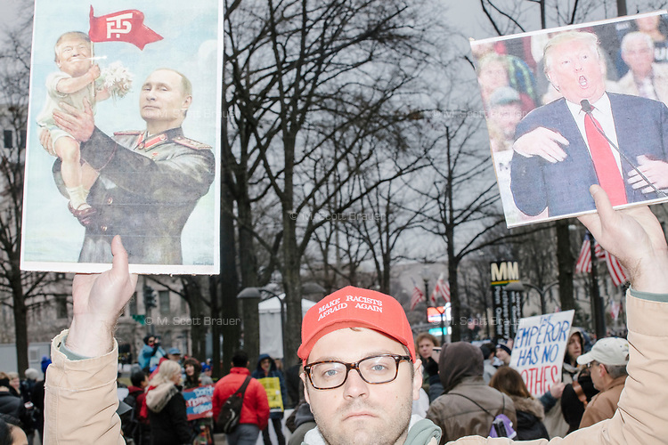 A man holds pictures of Donald Trump and Russian president Vladimir Putin in protest near the National Mall before the inauguration of President-elect Donald Trump on Jan. 20, 2017, in Washington, D.C.