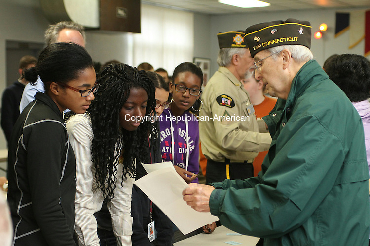 WATERTOWN, CT-05 November 2013-110513LW05 - Retired Navy Petty Officer Third Class Albert Cabana, 82, shows photos from his military days to Naugatuck High School students Harmony Sturdivant, 16, left, and Jendaya Bell, 17, center. Veterans spoke with students during a lunch at Oakville Veterans of Foreign Wars Post 7330 Thursday. Laraine Weschler Republican-American