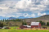 Beaverhead Valley Ranch. An iconic red barn decorates the valley floor beneath the towering peaks of western Montana; a wild sky adds to the landscape.