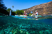 Kayakers paddling near the Captain Cook Monument at Kealakekua Bay, Big Island. Taken with underwater camera with image half below water.