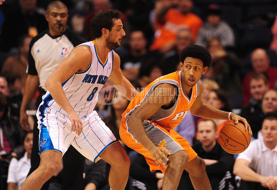 Dec. 26, 2011; Phoenix, AZ, USA; Phoenix Suns guard/forward Josh Childress (right) controls the ball against New Orleans Hornets guard Marco Belinelli at the US Airways Center. The Hornets defeated the Suns 85-84. Mandatory Credit: Mark J. Rebilas-USA TODAY Sports
