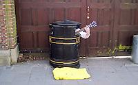 Enterprising busker inside a litter bin in Cambridge city centre.