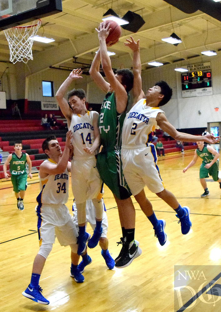 Photo by Mike Eckels<br /> <br /> Donell Kleiboeher (Pierce City #2) tries for a lay up against three Bulldogs defenders Jay Porter (#34, left), Troy Flood (#14) and Leng Lee (#2). The Bulldogs played the Eagles in the second round of the Battle at the Ridge basketball tournament at Pea Ridge High Dec. 11.