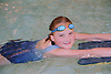 Young girl with complex congenital heart disease swimming in public swimming pool using float,