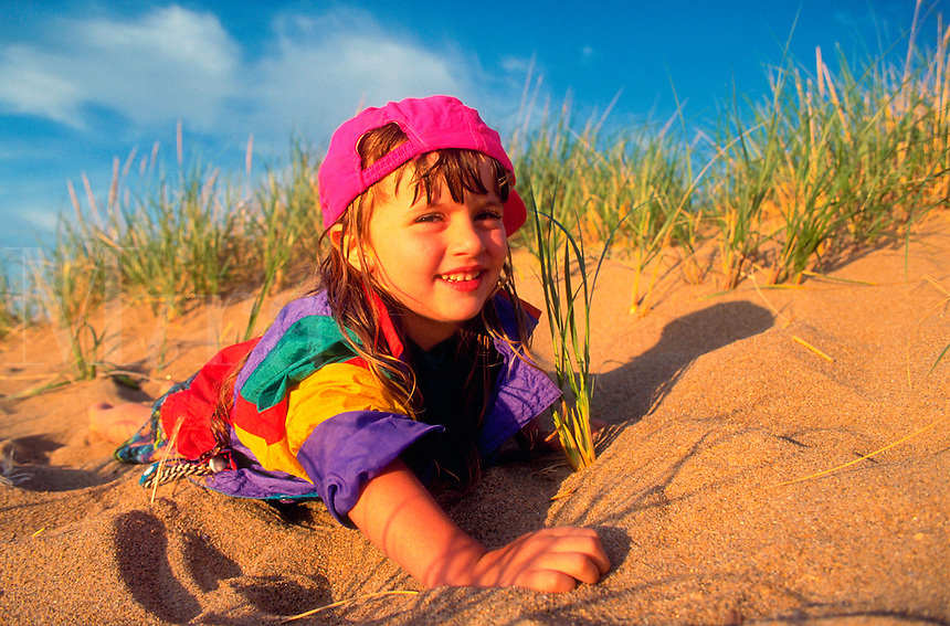 Portrait of smiling little girl wearing colorful clothing playing in the sand at a beach.
