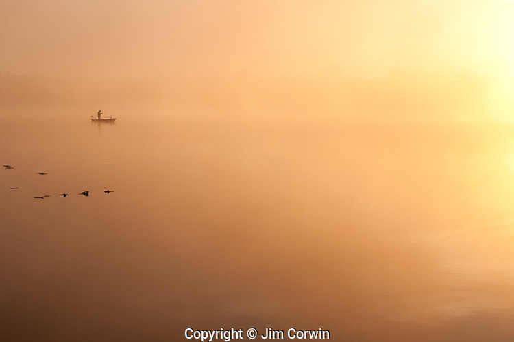 Sunrise Lake Cassidy in fog with fisherman in small boat fishing Snohomish County Washington State USA