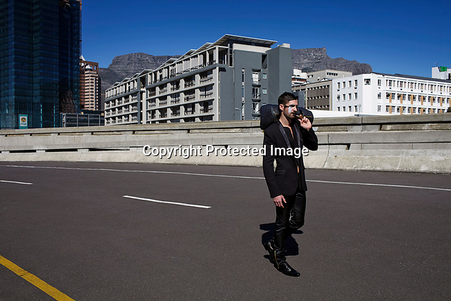CAPE TOWN, SOUTH AFRICA AUGUST 10: A model walking for the designer David Tlale waits for a show to start on a road on August 10 2013 in Cape Town, South Africa. David Tlale is one of South Africa's most established designers and he has shown at New York fashion week several times. He showed at the yearly Mercedes Benz Cape Town Fashion Week where some of South Africa's finest designers showed their 2012-13 spring and summer collections during the 4-day event. (Photo by Per-Anders Pettersson)